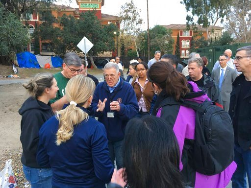 (AP Photo/Amy Taxin). Judge David Carter, a U.S. District Judge, center, followed by an entourage of three dozen lawyers, Orange County workers, nonprofit staff and local officials, tours a Southern California homeless encampment amid a lawsuit over ef...