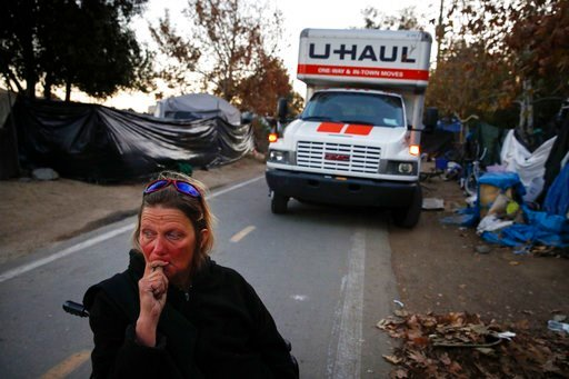 (AP Photo/Jae C. Hong, File). FILE - in this Jan. 22, 2018, file photo, Denise Lindstrom, a 49-year-old homeless woman, sits in a wheelchair with tearful eyes in front of a moving truck in an homeless encampment on the Santa Ana River trail in Anaheim,...