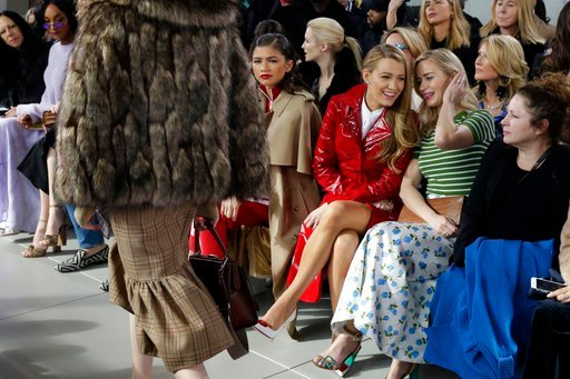 (AP Photo/Richard Drew). Blake Lively, third from right and Emily Blunt, second from right, talk as the Michael Kors collection is shown during Fashion Week in New York, Wednesday, Feb. 14, 2018.