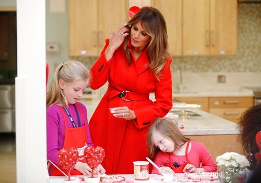 (AP Photo/Pablo Martinez Monsivais). First lady Melania Trump helps Annie Ribas, 9, left, and Katherine Faughn, 6, right, decorate cookies during her visit to the Children's Inn at the National Institute of Health, Wednesday, Feb. 14, 2018, in Bethesda...