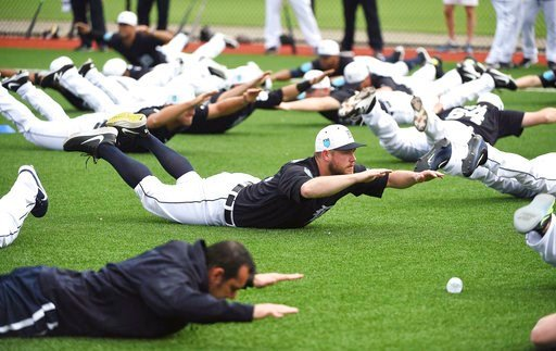 (Robin Buckson/Detroit News via AP). Detroit Tigers pitcher Alex Wilson does an exercise with the rest of the players during spring baseball practice, Wednesday, Feb. 14, 2018 in Lakeland, Fla.