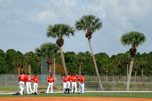 (AP Photo/Jeff Roberson). Members of the Miami Marlins pause before stretching during spring training baseball practice Wednesday, Feb. 14, 2018, in Jupiter, Fla.