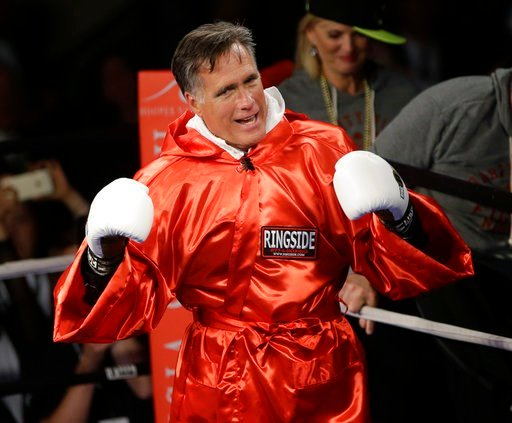 (AP Photo/Rick Bowmer, File). FILE - In this May 15, 2015, file photo, former Republican presidential candidate Mitt Romney raises his gloves before sparring with five-time heavyweight boxing champion Evander Holyfield during a charity fight event, in ...