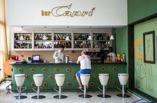 (AP Photo/Desmond Boylan). FILE - In this Sept. 12, 2017, file photo, a customer sits at the lobby bar of the Hotel Capri in Havana, Cuba. Doctors are releasing the first detailed medical reports about the hearing, vision, balance and brain symptoms su...