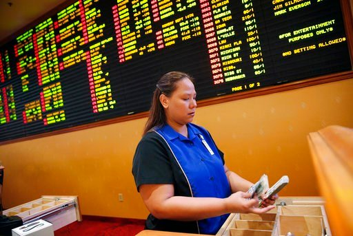 (AP Photo/John Locher, File). FILE - In this Aug. 20, 2015, file photo, Therese Duenas counts money as she takes bets in the sports book at the South Point hotel and casino in Las Vegas. Jersey has challenged the Professional and Amateur Sports Protect...