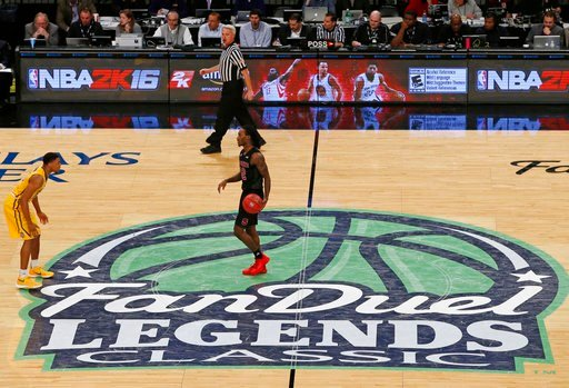 (AP Photo/Kathy Willens, File). FILE - In this Nov. 24 2015, file photo, North Carolina State guard Anthony Barber dribbles the ball across the FanDuel logo during an NCAA college basketball game in the Legends Classic in New York. The explosion in pop...