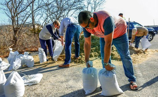 (Greg Derr/The Quincy Patriot Ledger via AP). Robin King grabs sandbags to use at his restaurant, Thursday, March 1, 2018, in Scituate, Mass., ahead of Friday's expected storm, predicted to bring high winds and the potential for coastal flooding.