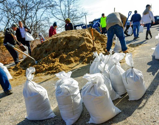 (Greg Derr/The Quincy Patriot Ledger via AP). Residents and business owners collect sandbags, Thursday, March 1, 2018, in Scituate, Mass., ahead of Friday's expected storm, predicted to bring high winds and the potential for coastal flooding.