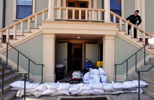 (Steve Heaslip/The Cape Cod Times via AP). Provincetown DPW worker Paulo Andrade moves sand bags around the lower entrance to town hall as preparations are underway for the approaching storm, Thursday, March 1, 2018 in Provincetown, Mass.