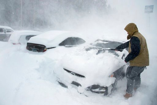 (Randy Pench/The Sacramento Bee via AP). Heavy winds blow snow as Ryan Foster, 25, scrapes snow from his car in the parking lot where he lives at the Donner Summit Lodge in Norden on Thursday, March 1, 2018, near Donner Summit, Calif. A major winter st...