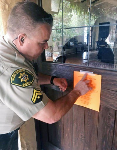 (Mike Eliason/Santa Barbara County Fire Department via AP). Santa Barbara County Sheriff's Deputy Mike Harris posts a notice on a home near Carpinteria, Calif., advising of the mandatory evacuation notice due to forecast rain and possible debris flow d...