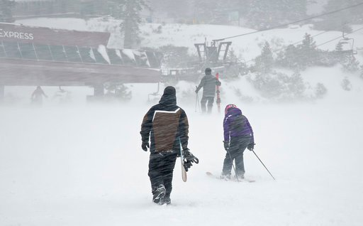 (Northstar California via AP). In this photo provided by Northstar California, a snowboarder and pair of skiers make their way through gusts of wind to a lift Thursday, March 1, 2018, at the Northstar California resort in Truckee, Calif. A major winter...