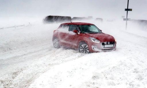 (Owen Humphreys/PA via AP). Cars in snowy conditions on the A192 road near Blyth, north east England, Thursday March 1, 2018. Persistent snow and freezing conditions are causing delays in many parts of Britain, with roads and train service hit particul...