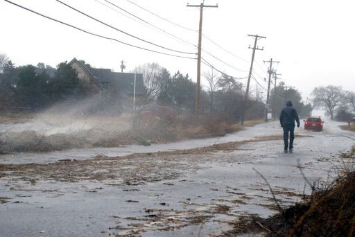 (AP Photo/Elise Amendola). A pedestrian walks down a flooded roadway towards Plum Island Friday, March 2, 2018, in Newburyport, Mass., as a major nor'easter pounds the East Coast, packing heavy rain, intermittent snow and strong winds. The Eastern Seab...
