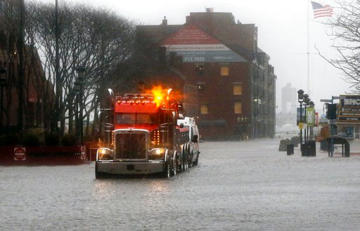 (AP Photo/Bill Sikes). A wrecker tows a vehicle stranded on State Street by water from Boston Harbor at high tide during a major nor'easter that pounded the East Coast, Friday, March 2, 2018, in Boston.