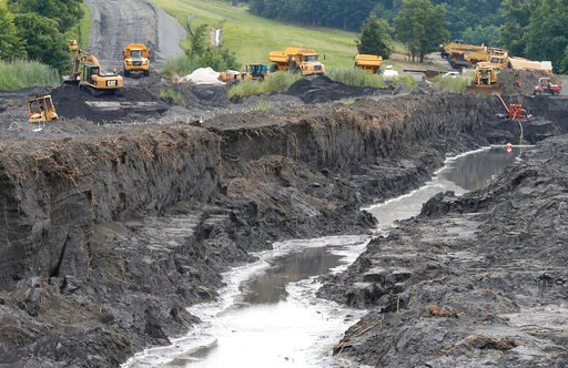 (AP Photo/Steve Helber, File). FILE- In this June 26, 2015 file photo, trucks haul coal ash from one retention pond to a permanent pond at the Dominion Power's Possum Point Power Station in Dumfries, Va. Major utilities are finding evidence of groundwa...