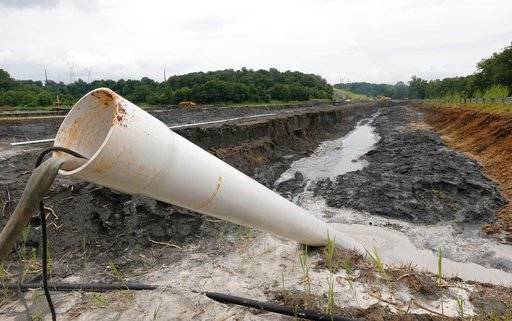(AP Photo/Steve Helber, File). FILE - In this Friday June 26, 2015 file photo, a drain pipe sticks out of a coal ash retention pond at the Dominion Power's Possum Point Power Station in Dumfries, Va. Major utilities are finding evidence of groundwater ...