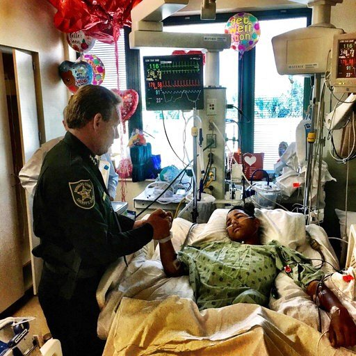 (Broward County Sheriff's Office via AP). This image made available by the Broward County Sheriff's Office on Sunday, Feb. 18, 2018, shows Sheriff Scott Israel, holding the hand of Anthony Borges, 15, a student at Marjory Stoneman Douglas High School. ...