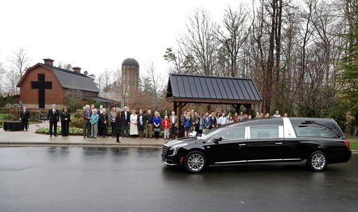 (AP Photo/Chuck Burton). Family members look on as the hearse carrying the body of the Rev. Billy Graham returns to the Billy Graham Library in Charlotte, N.C., Thursday, March 1, 2018. His funeral will be Friday.