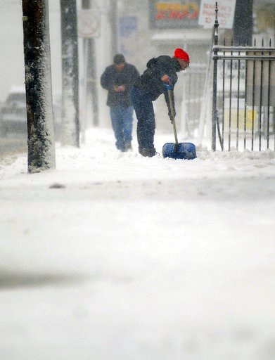 (Butch Comegys/The Times-Tribune via AP). A resident shovels snow along Main Street in Peckville, Pa., Friday, March 2, 2018.