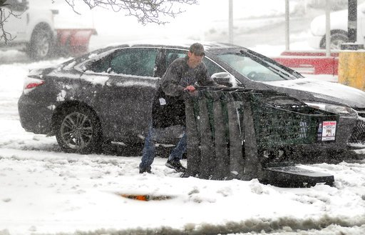 (Butch Comegys/The Times-Tribune via AP). An employee for Quinn's Market in Peckville, Pa., collects shopping carts in the parking lot Friday, March 2, 2018. The store lost power and was closed for several hours.