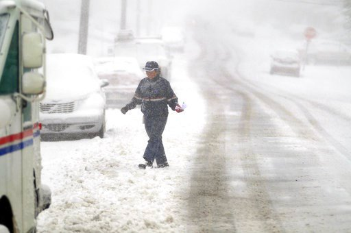 (Butch Comegys/The Times-Tribune via AP). A U.S. Postal Service mail carrier walks during a snowstorm on Third Street in Blakely, Pa., Friday, March 2, 2018. A relentless nor'easter pounded the Atlantic coast with hurricane-force winds and sideways-blo...