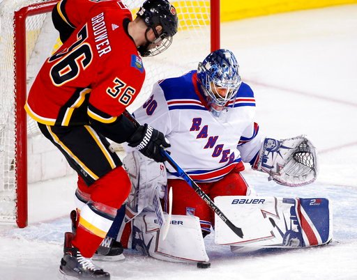 (Larry MacDougal/The Canadian Press via AP). New York Rangers goalie Henrik Lundqvist, right, of Sweden, makes a save against Calgary Flames' Troy Brouwer during first-period NHL hockey game action in Calgary, Alberta, Friday, March 2, 2018.