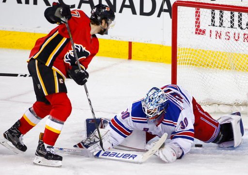 (Larry MacDougal/The Canadian Press via AP). New York Rangers goalie Henrik Lundqvist, right, of Sweden, makes a save against Calgary Flames' Michael Frolik, of the Czech Republic, during second-period NHL hockey game action in Calgary, Alberta, Friday...