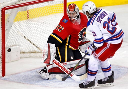(Larry MacDougal/The Canadian Press via AP). New York Rangers' Ryan Spooner, right, scores against Calgary Flames goalie Jon Gillies during second-period NHL hockey game action in Calgary, Alberta, Friday, March 2, 2018.