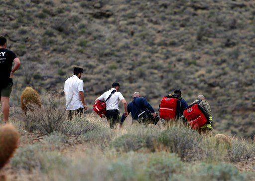 (Teddy Fujimoto via AP, File). FILE - In this Saturday, Feb. 10, 2018, file photo, emergency personnel arrive at the scene of a deadly tour helicopter crash along the jagged rocks of the Grand Canyon, in Arizona. The parents of a British tourist who di...