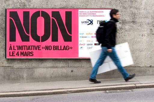 "(Anthony Anex/Keystone via AP). FILE - In this Feb. 9, 2018 photo a man passes by a sign asking to vote in the ""No Billag"" initiative in Fribourg, Switzerland. Swiss voters can decide in a referendum on March 4, 2018 on a proposal to stop the mandatory..."