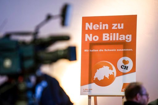 (Peter Schneider/Keystone via AP). FILE - In this Jan. 27, 2018 file photo a poster against the 'No Billag' initiative is displayed at a meeting of the Christian Democratic party CVP in Bern, Switzerland. Swiss voters can decide in a referendum on Marc...