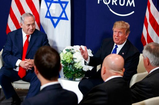 (AP Photo/Evan Vucci). FILE - In this Jan. 25, 2018 file photo, Israeli Prime Minister Benjamin Netanyahu looks on as President Donald Trump speaks during a meeting at the World Economic Forum in Davos.  In the foreground from left are White House seni...