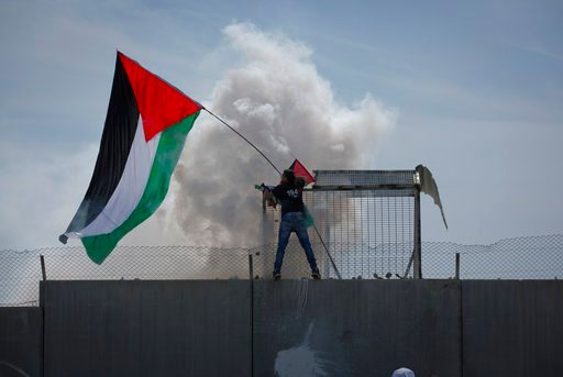 (AP Photo/Nasser Nasser). Israeli border police uses teargas to disperse a protester who climbed a section of the Israeli separation barrier waving a Palestinian flag, during a protest in the West Bank village of Bil'in, west of Ramallah, Friday, March...