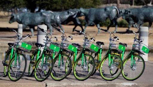 (AP Photo/Tony Gutierrez). In this Feb. 8, 2018 photo, shared bikes ready to be used are lined up on a sidewalk by a popular tourist destination in Dallas. Shared bikes that can be left wherever the rider ends up are helping more people get access to t...