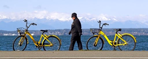"(AP Photo/Elaine Thompson). In this Feb. 22, 2018 photo, a pedestrian walks past a pair of ""dockless"" bicycles parked next to a sidewalk in Seattle. Shared bikes that can be left wherever the rider ends up are helping more people get access to the mode..."