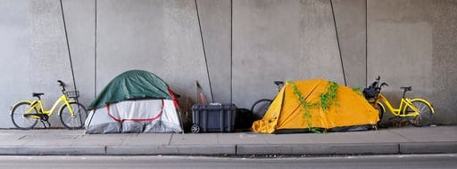 "(AP Photo/Elaine Thompson). In this photo taken Feb. 22, 2018, two ""dockless"" bicycles bookend a pair of tents where people are camped on a sidewalk in Seattle. Shared bikes that can be left wherever the rider ends up are helping more people get access..."