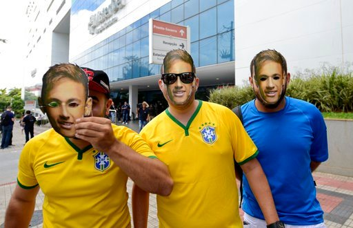 (AP Photo/Eugenio Savio). Supporters wear soccer star Neymar face masks as they pose for a photo at the Mater Dei Hospital, in Belo Horizonte, Brazil, Saturday, March 3, 2018. Neymar will have surgery on a fractured toe in his right foot and could be o...