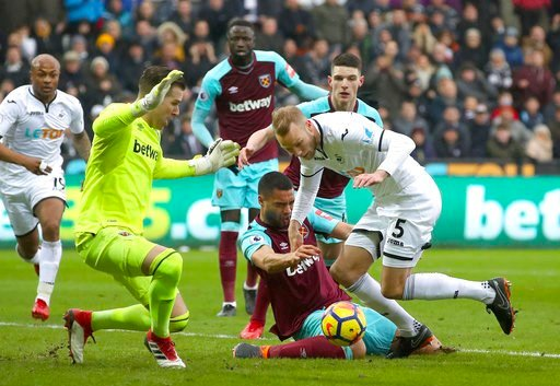 (Nick Potts/PA via AP). West Ham United's Winston Reid, centre, and Swansea City's Mike van der Hoorn, right, in action during their English Premier League soccer match at the Liberty Stadium in Swansea, England, Saturday March 3, 2018.