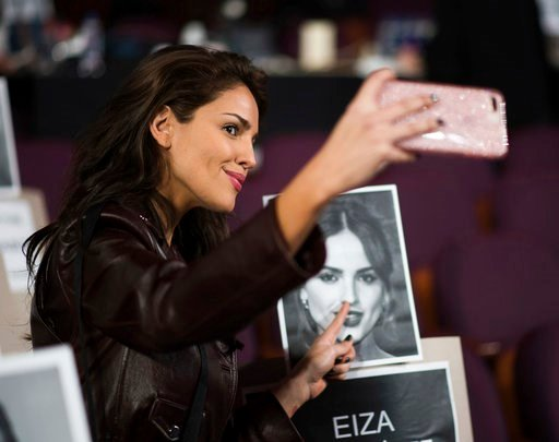 (Photo by Charles Sykes/Invision/AP). Eiza Gonzalez takes a photo with her placeholder during rehearsals for the 90th Academy Awards in Los Angeles on Saturday, March 3, 2018. The Academy Awards will be held at the Dolby Theatre on Sunday, March 4.