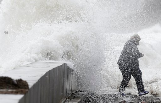 (AP Photo/Michael Dwyer). A woman gets caught by a wave as heavy seas continue to come ashore in Wintrhrop, Mass., Saturday, March 3, 2018, a day after a nor'easter pounded the Atlantic coast with hurricane-force winds.