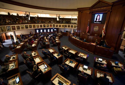 (AP Photo/Mark Wallheiser, File). In this Feb. 21, 2018, file photo, the Florida Senate chamber is darkened while a slideshow shows each person killed in a shooting at Marjory Stoneman Douglas High School, at the state Capitol in Tallahassee, FL.