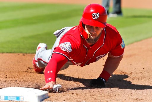 (AP Photo/Jeff Roberson). Washington Nationals' Bryce Harper dives back to first on a pickoff attempt during the fourth inning of an exhibition spring training baseball game against the Houston Astros Saturday, March 3, 2018, in West Palm Beach, Fla.