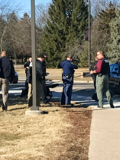 (Lisa Yanick Litwiller /The Morning Sun via AP). Authorities gather on the campus of Central Michigan University during a search for a suspect, in Mount Pleasant, Mich., Friday, March 2, 2018.