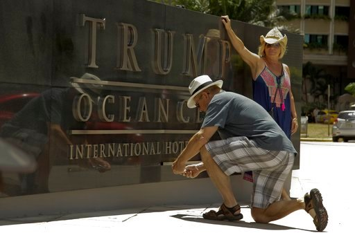 (AP Photo/Arnulfo Franco, File). FILE - In this Feb. 27 ,2018 file photo, Tourists take photographs of the marquee at the main entrance of the Trump Ocean Club International Hotel and Tower in Panama City.  The hotel remains open for business against a...
