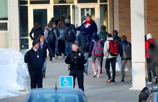 (David Joles/Star Tribune via AP). In this Feb. 22, 2018 photo, police officers stand guard as Orono High School students arrive for school, one day after a threat was posted, causing the school to go on lockdown in Orono, Minn. An autistic Orono High ...