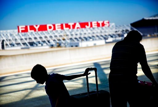 (AP Photo/David Goldman, File). FILE- In this Oct. 13, 2016, file photo, passengers unload in front of a Delta Air Lines sign at Hartsfield-Jackson Atlanta International Airport, in Atlanta. Georgia lawmakers punished Atlanta-based Delta Air Lines on T...