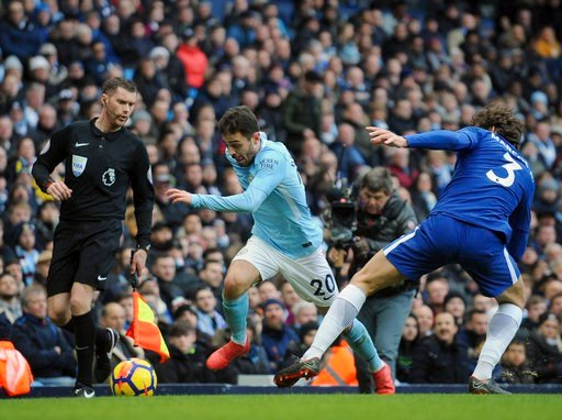 (AP Photo/Rui Vieira). Manchester City's Bernardo Silva, center, challenges for the ball with Chelsea's Marcos Alonso during the English Premier League soccer match between Manchester City and Chelsea at the Etihad Stadium in Manchester, England, Sunda...