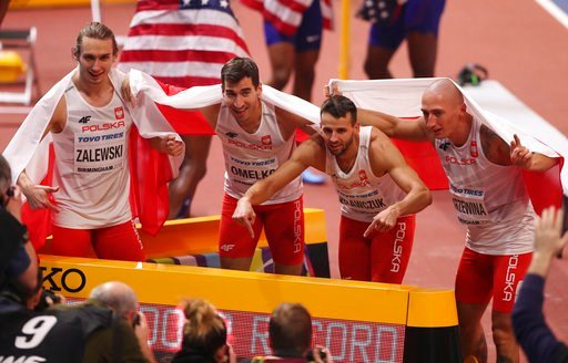 (AP Photo/Alastair Grant). Poland's Karol Zalewski, Rafal Omelko, Lukasz Krawczuk and Jakub Krzewina, from left, celebrate after setting a new World Indoor Record when winning the gold medal in the men's 4x400-meter relay final at the World Athletics I...