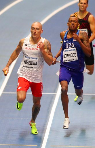 (AP Photo/Alastair Grant). Poland's Jakub Krzewina, left, passes by United States' Vernon Norwood when winning the gold medal in the men's 4x400-meter relay final at the World Athletics Indoor Championships in Birmingham, Britain, Sunday, March 4, 2018.